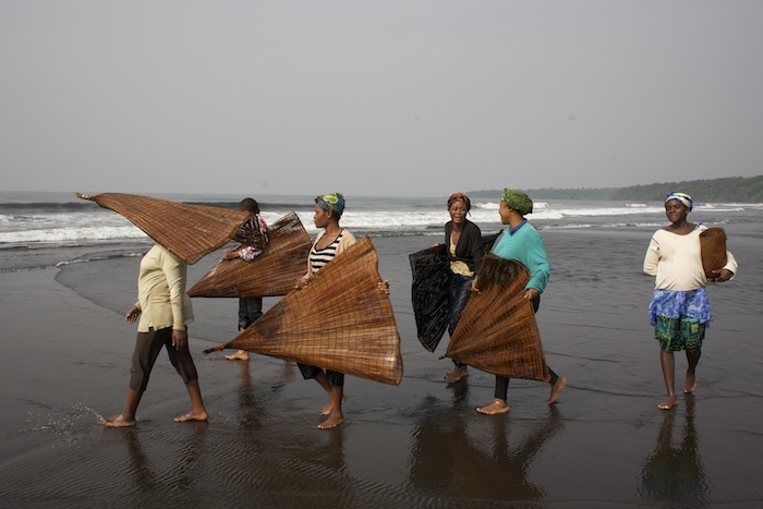 A village rests in the middle of the forest reserve.  The women of the village fish for sardines in the surf with cone shaped traps.